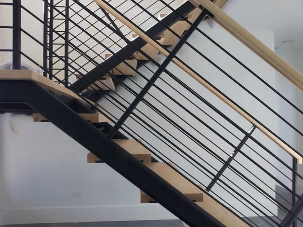 This modern steel stair features wood treads spanning between steel channels. Steel rods are provided instead of the standard cable rail. Photo 7 of Lake Washington Home modern home