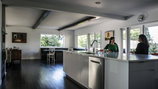 The spacious kitchen is sensible but definitely not boring with glossy white counter tops and cabinets that contrast with the dark flooring. Photo 4 of Mod Remodel modern home