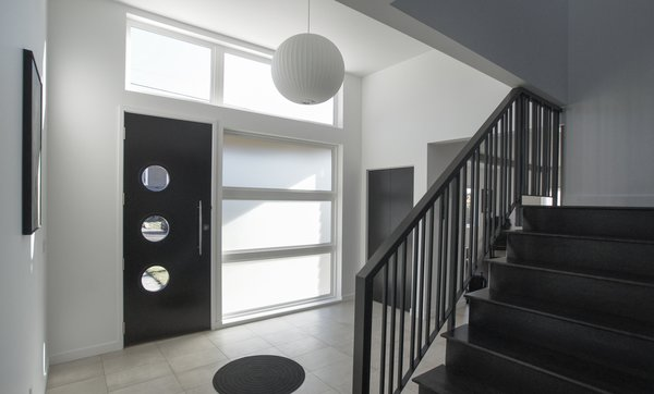 The interior of the home is filled with unique touches like circular windows and lamps grounded in a classic black and white color scheme that make the house stylish without being kitschy. Photo 7 of Mod Remodel modern home