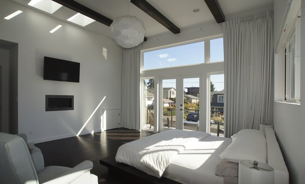 The master bedroom embraces the sophistication that comes with simplicity. The wide windows and glass doors let light stream into the room and create a connection to the rest of the beautiful Kirkland neighborhood and the view beyond. Photo 8 of Mod Remodel modern home