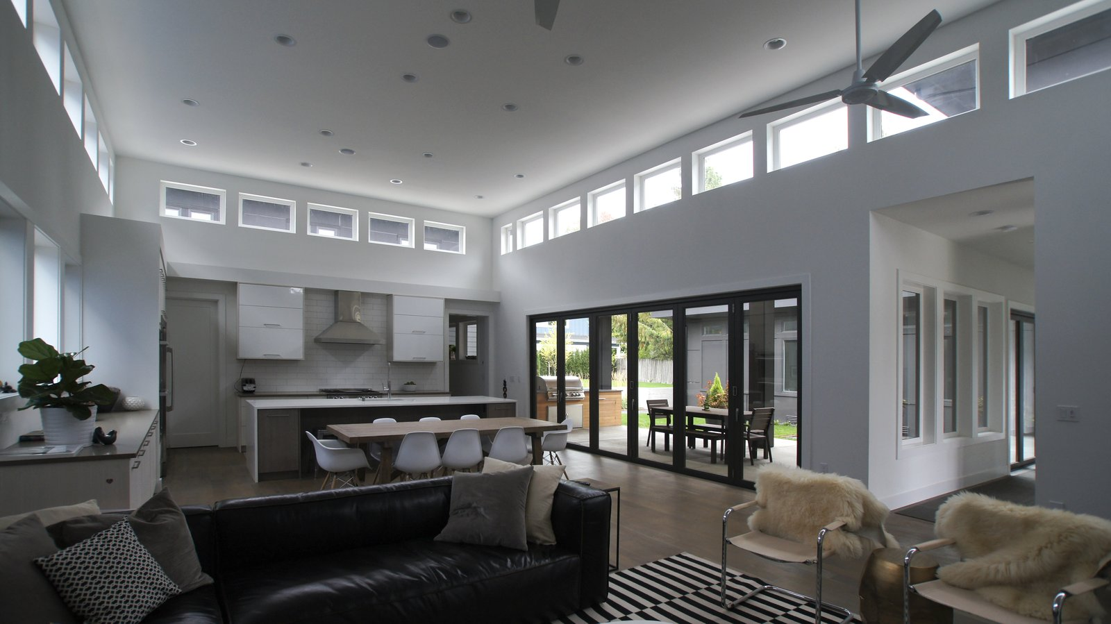High ceilings were a priority for the clients and the clerestory windows create an illusion that extends the ceiling even higher. Direct access to the deck through the glass doors opens the space even further and seamlessly connects one room to another.  Modern Courtyard Home by Atelier Drome