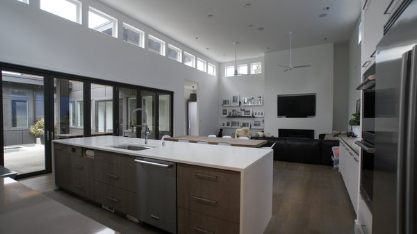 The large kitchen island is perfect area to gather around for special occasions or for daily activities like homework for the kids. There is plenty of built in storage space for storing kitchenware. Photo 3 of Modern Courtyard Home modern home