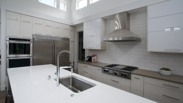 A neutral color palette is modernized with glossy finishes, a subway tile backsplash, and stainless appliance accents. This is a kitchen that will highlight and draw attention to the food, becoming a blank canvas for the owners to personalize. Photo 5 of Modern Courtyard Home modern home
