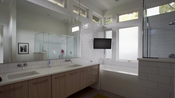 The master bathroom is a light-filled space of relaxation with a large bathtub as well a spacious shower. The tile backsplash provides a modern finish and every convenience was added to truly make this a room of leisure. Photo 6 of Modern Courtyard Home modern home