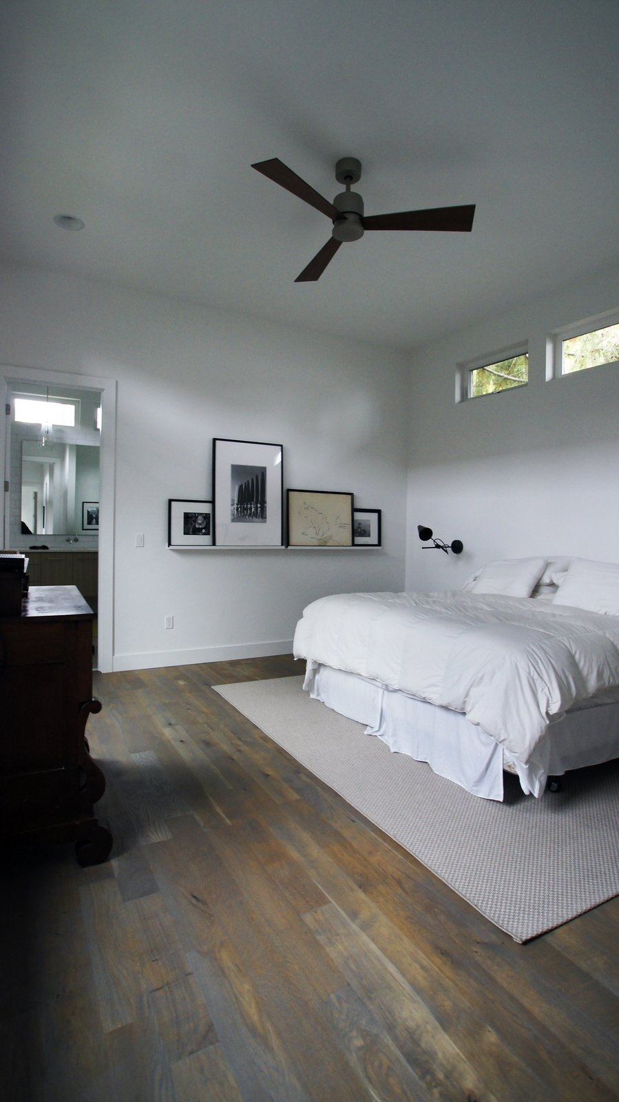 The master bedroom is a clean but cozy space filled with plenty of light from the clerestory windows.  Modern Courtyard Home by Atelier Drome