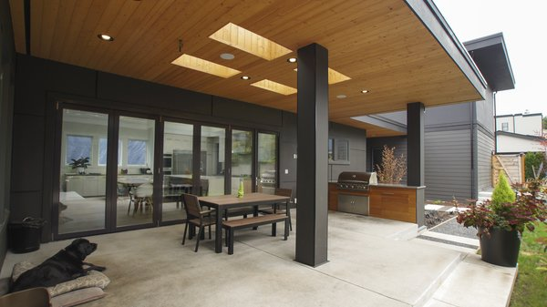 The covered patio and built-in barbecue make the backyard perfect for outdoor living. Photo 11 of Modern Courtyard Home modern home