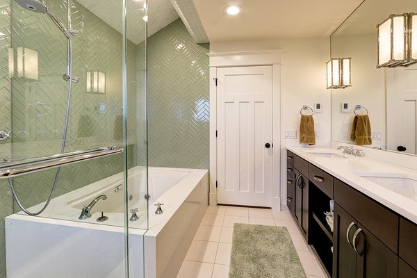 Modern home with bath room, enclosed shower, soaking tub, corner shower, ceramic tile wall, drop in sink, accent lighting, and wall lighting. Photo 5 of West Seattle View Home