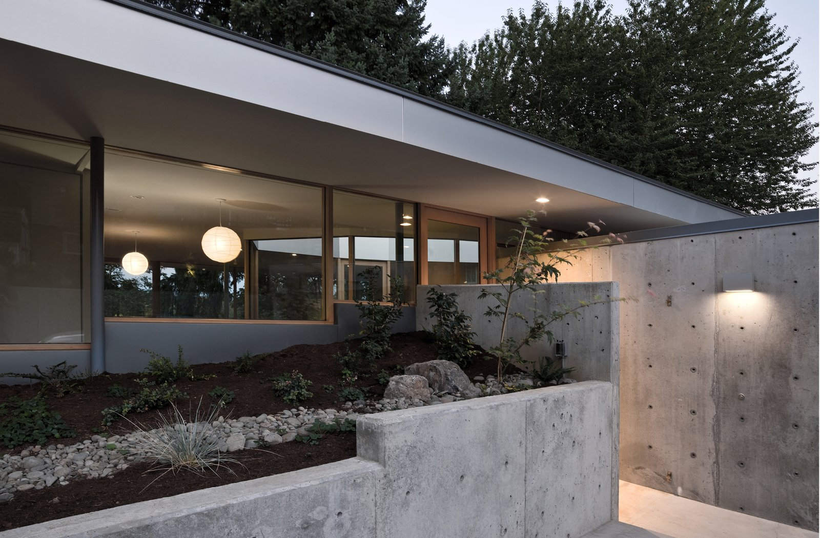 Entered through a sunken patio, the house flows in a continuous loop around two L-shaped storage cores.
