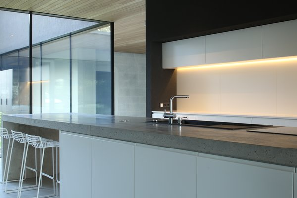 Open kitchen with view to the atrium and cherry trees  Photo 2 of Karhusaari modern home