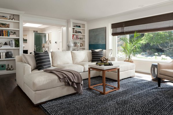 Modern home with living room, bookcase, sectional, and coffee tables. Living room. Interior design by Carrington Hill Designs. Photo  of Atherton Home Design Makeover