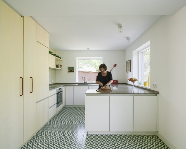 Modern home with kitchen, engineered quartz counter, cement tile floor, white cabinet, wood cabinet, wood backsplashe, drop in sink, and ceiling lighting. kitchen Photo 15 of Haus Mai