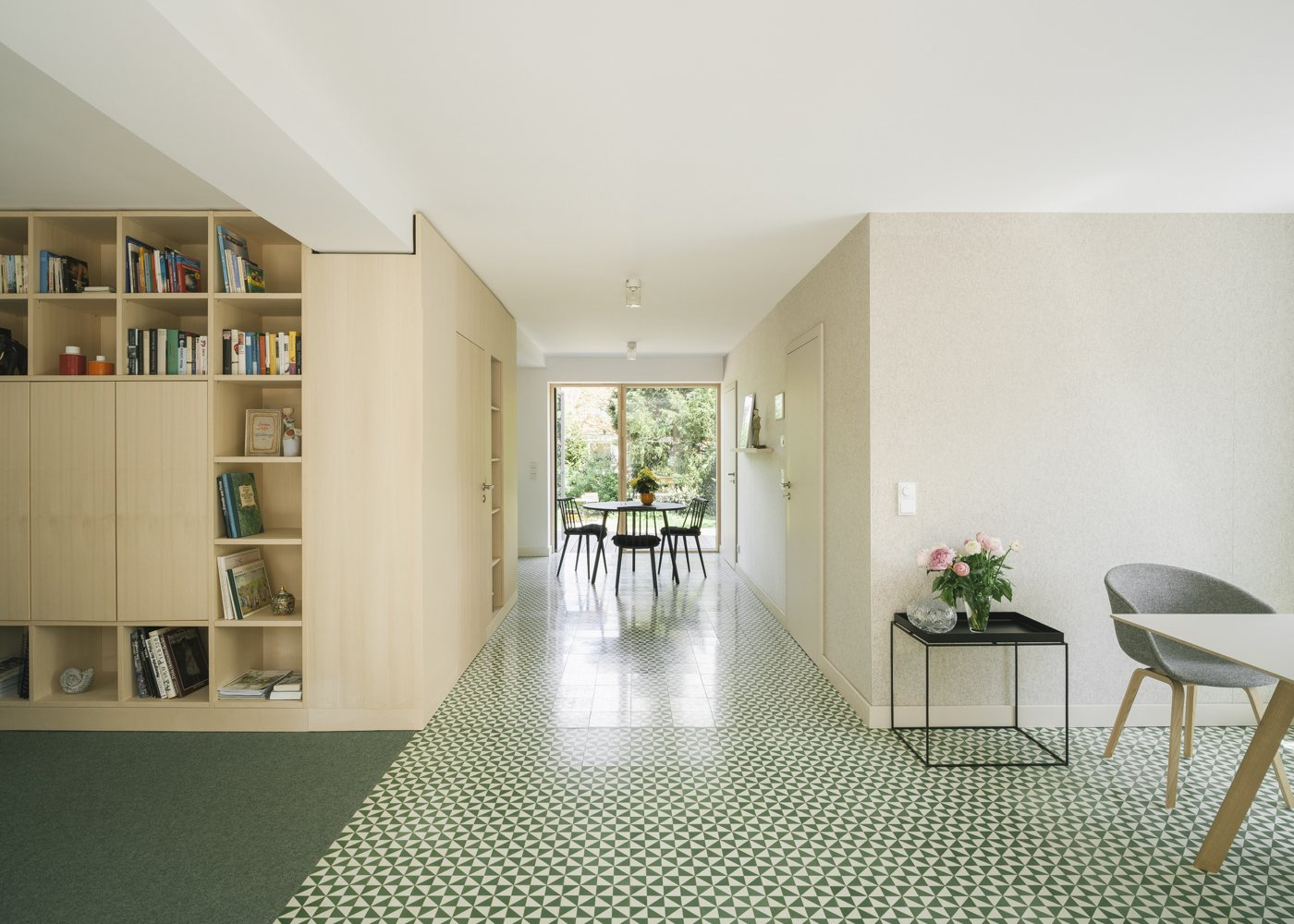 open plan living room Tagged: Cement Tile Floor, Carpet Floor, Shelves, Storage, Chair, and Dining Room. Haus Mai by Project Architecture Company