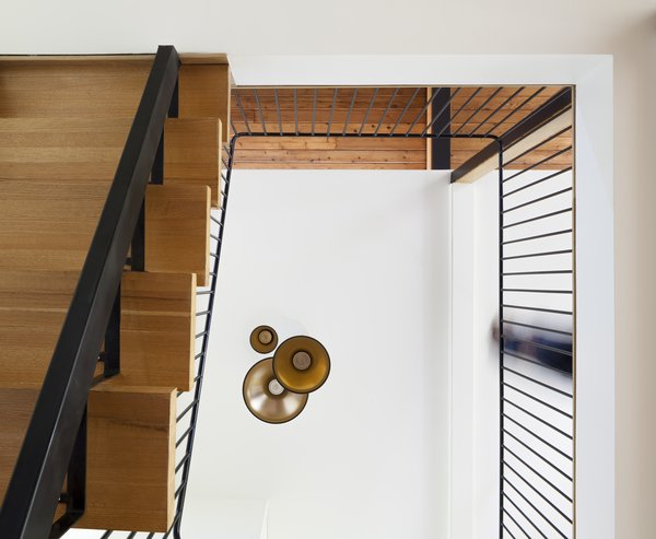Modern home with metal tread, wood tread, metal railing, living room, pendant lighting, and ceiling lighting. Staircase - Rue de l'Espéranto residence  - Guillaume Sasseville & PARKA - Architecture & Design Photo 12 of Rue de l'Espéranto residence