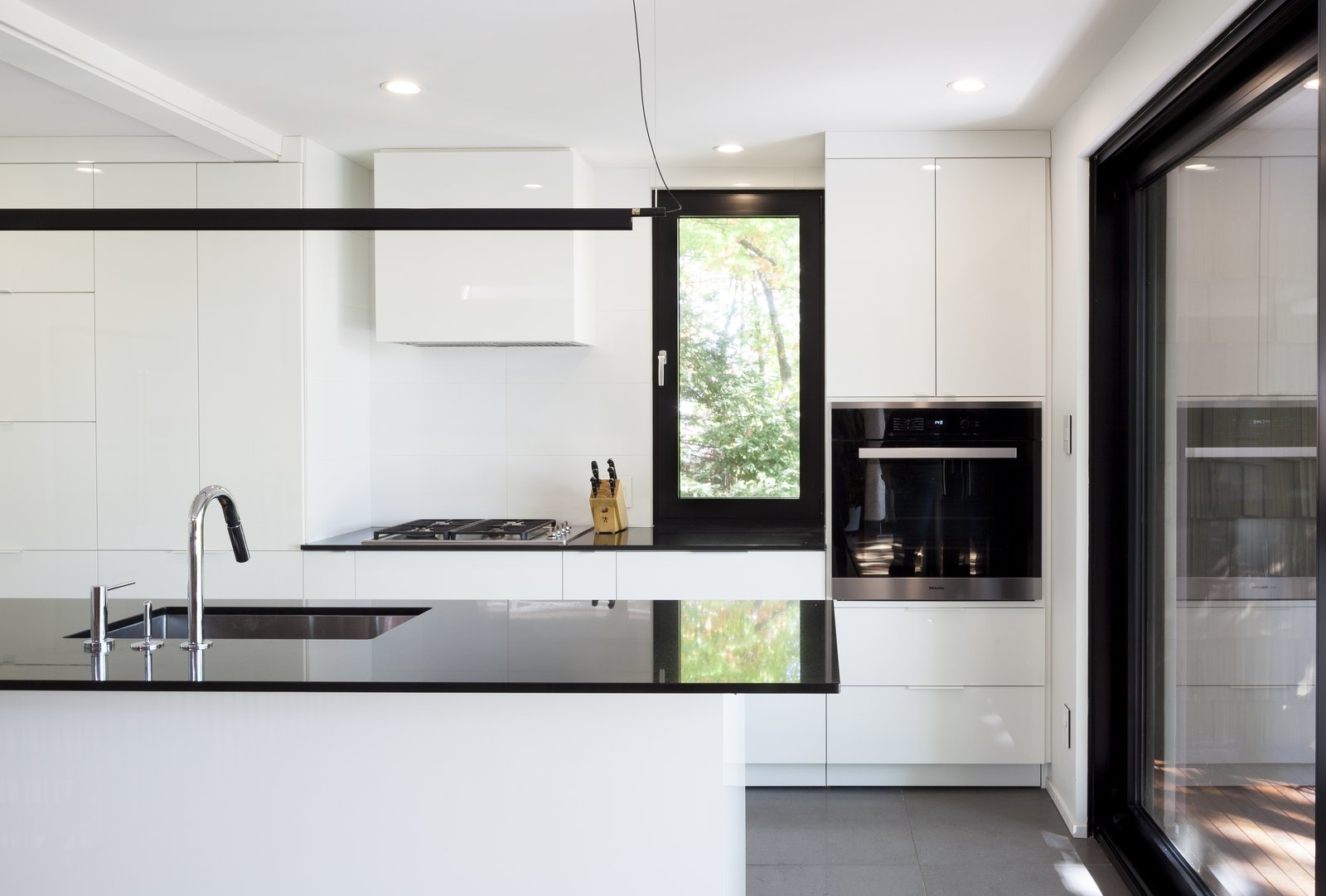 Kitchen - Rue de l'Espéranto residence  - Guillaume Sasseville & PARKA - Architecture & Design Tagged: Kitchen, White, Ceiling, Ceramic Tile, Ceramic Tile, Track, Pendant, Wall Oven, Undermount, and Cooktops.  Best Kitchen White Track Photos from Rue de l'Espéranto residence