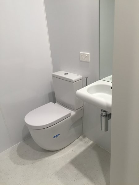 A simple  minimalist bathroom; toilet, sink with mirror, and shower opposite. Photo 5 of The Tiny house modern home