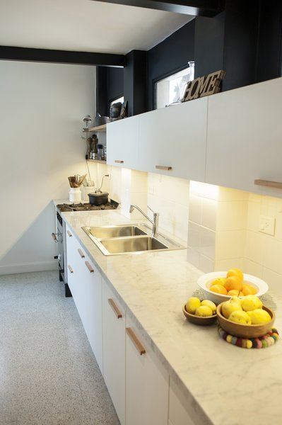 Marble countertop, granite floors, white furniture and wooden details. Photo 3 of Artigas modern home