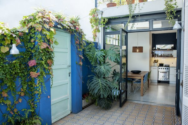 The patio at the front offers a view to the dining area and kitchen. It has been painted in blue , which highlights the antique floor. Photo 9 of Artigas modern home