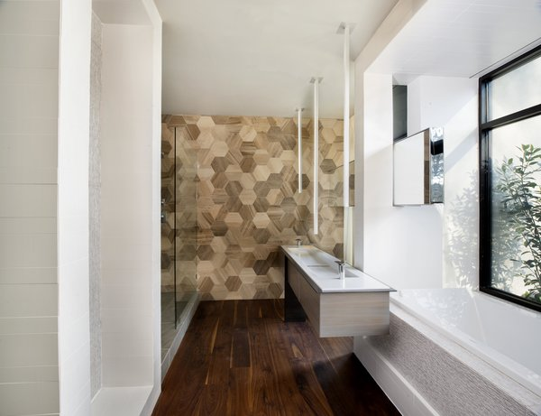 Modern home with bath room and dark hardwood floor. Highly-engineered floating steel and wood bath vanity/sink designed by West Architecture Studio and fabricated by Luke Prestridge and Timberland Cabinetry.  Custom mirror that also acts  as tub filler. Photo 5 of Alaska House