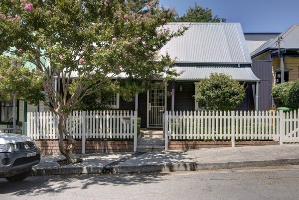 The original cottage sits comfortably within the streetscape, set behind a Crepe Myrtle tree. Photo  of Inner West House modern home