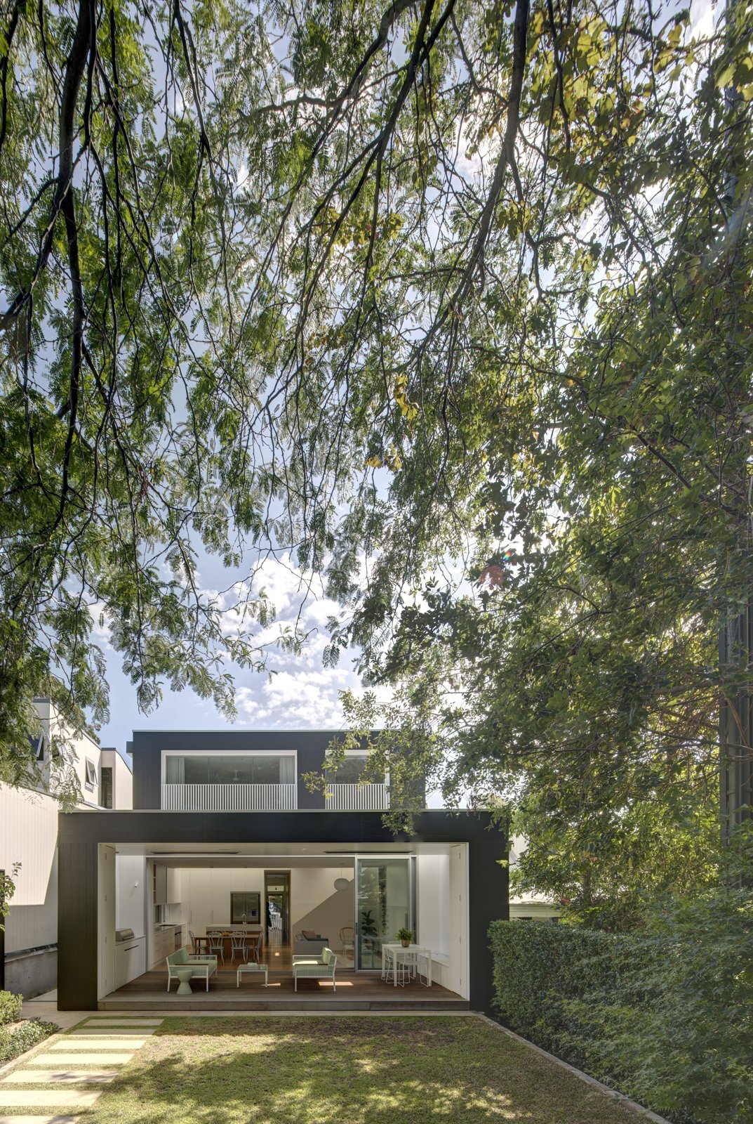 The rear of the house opens to the garden, creating a layering of spaces from inside to out.