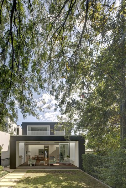 Modern home with outdoor, back yard, trees, shrubs, walkways, and grass. The rear of the house opens to the garden, creating a layering of spaces from inside to out. Photo 2 of Inner West House