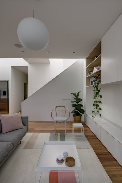 Modern home with living room, sofa, chair, coffee tables, bookcase, ceiling lighting, and medium hardwood floor. Colourful furnishings animate the space. Thonet armchair, Jardan Nook lounge and Hay side tables provide a comfortable, deliberately low key setting. Photo 4 of Inner West House