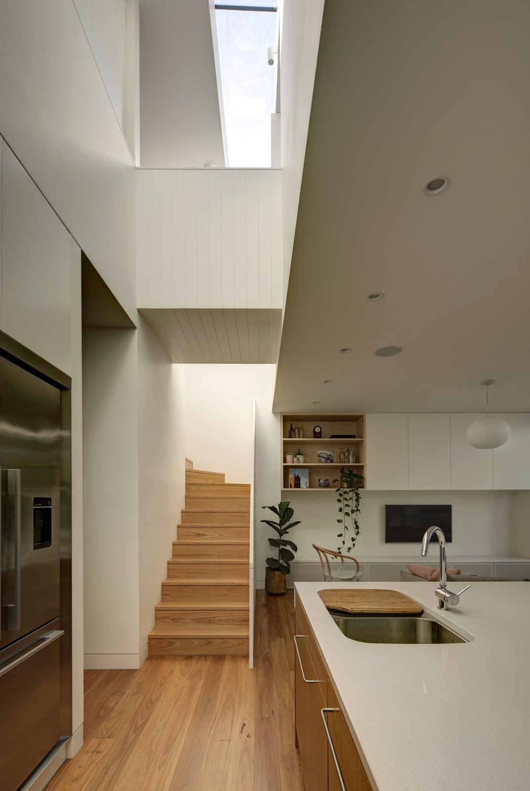 A bridge spans across the two-storey void that cuts across the house, drawing natural light into the interiors and creating connection between ground floor and the upper level.  Inner West House by Andrew Burns