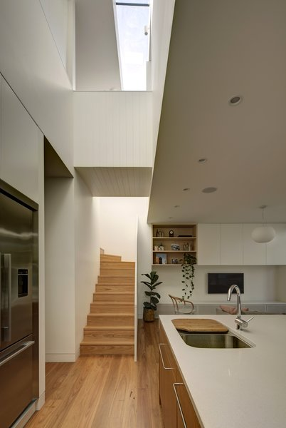 A bridge spans across the two-storey void that cuts across the house, drawing natural light into the interiors and creating connection between ground floor and the upper level. Photo 5 of Inner West House modern home