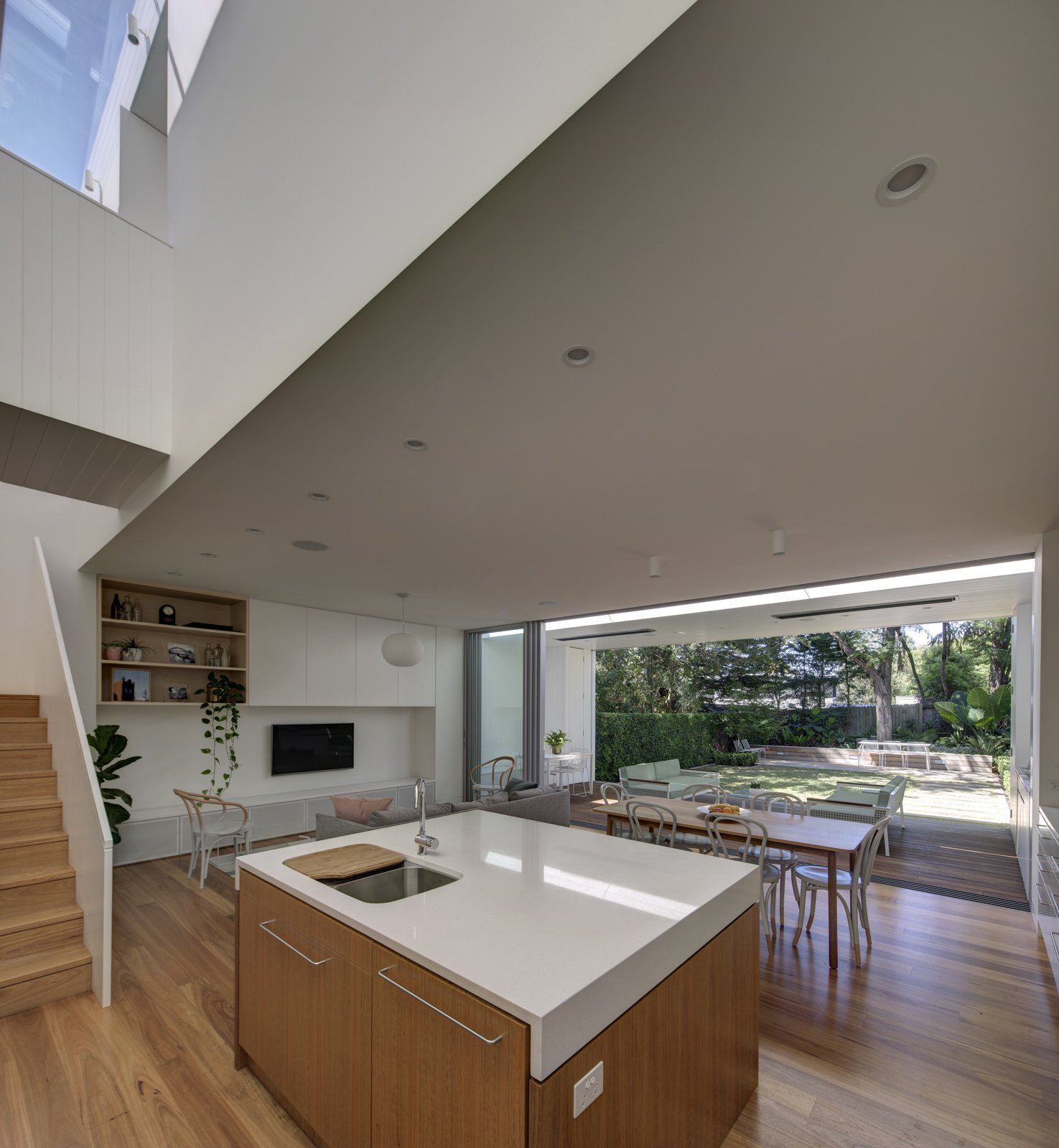 The view to the garden is across a sequence of spaces - the kitchen / living / dining spaces extend onto a covered loggia, a thermally controlled indoor / outdoor space for year round comfort.  Inner West House by Andrew Burns