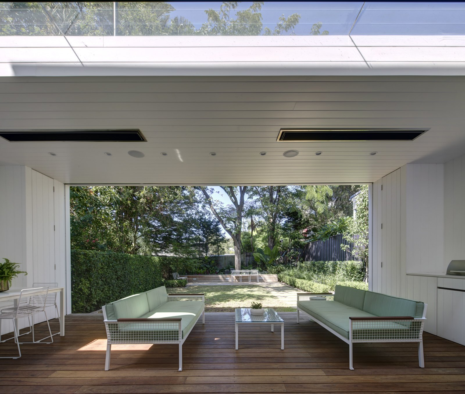 The garden room frames the landscape and becomes an extension of the interior spaces. White painted lining boards wrap the space and echo the traditional palette of the cottage.  Inner West House by Andrew Burns