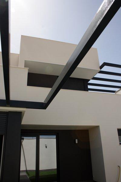 Modern home with outdoor and back yard. Perogolas, volúmenes de planta superior desde el patio. Photo 4 of CASA FLORES