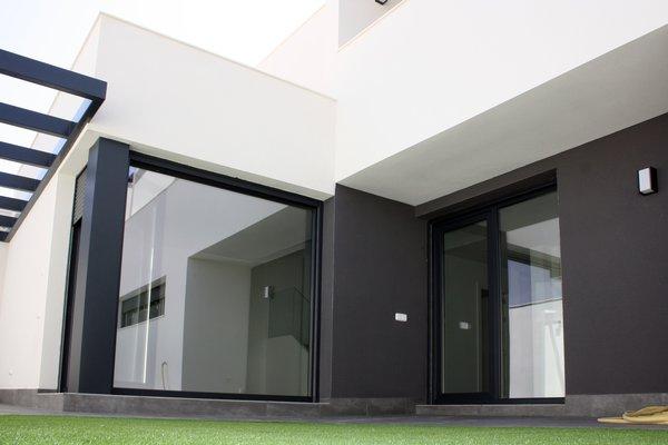 Modern home with outdoor, back yard, small patio, porch, deck, stone patio, porch, deck, garden, and grass. Cristalera de acceso al patio. Photo 5 of CASA FLORES