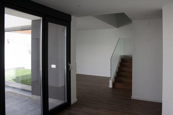 Modern home with living room, medium hardwood floor, and ceiling lighting. Volumetria con doble altura en el salón. Photo 8 of CASA FLORES