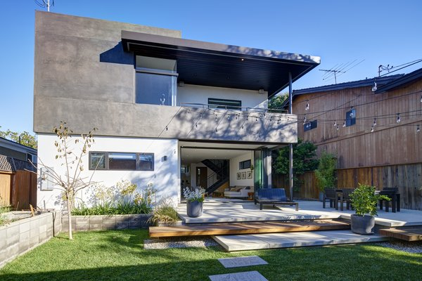Modern home with front yard, shrubs, grass, hardscapes, chair, sofa, ceiling lighting, ceramic tile floor, bed, dresser, dark hardwood floor, wood tread, metal railing, coffee tables, bench, pendant lighting, and outdoor. Photo 7 of Project Coalesce