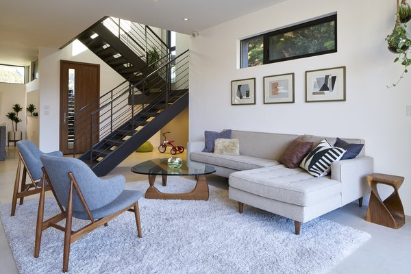 Modern home with front yard, shrubs, sofa, ceiling lighting, grass, hardscapes, chair, ceramic tile floor, dresser, dark hardwood floor, wood tread, bed, metal railing, and living room. Photo 5 of Project Coalesce