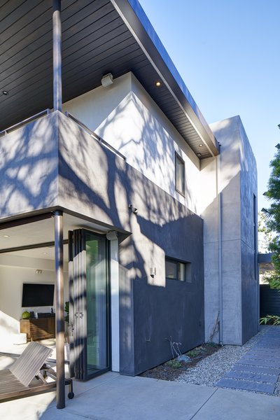 Modern home with chair, sofa, ceiling lighting, bed, dresser, wood tread, ceramic tile floor, dark hardwood floor, metal railing, bench, pendant lighting, back yard, concrete patio, porch, deck, coffee tables, grass, and outdoor. Photo 14 of Project Coalesce