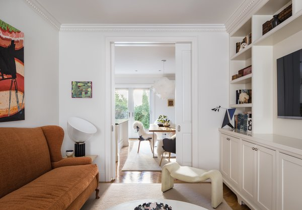 Modern home with end tables, swing door type, medium hardwood floor, standard layout fireplace, wall lighting, interior, accent lighting, table lighting, chair, coffee tables, sofa, bookcase, and living room. Photo 3 of Greenpoint Townhouse