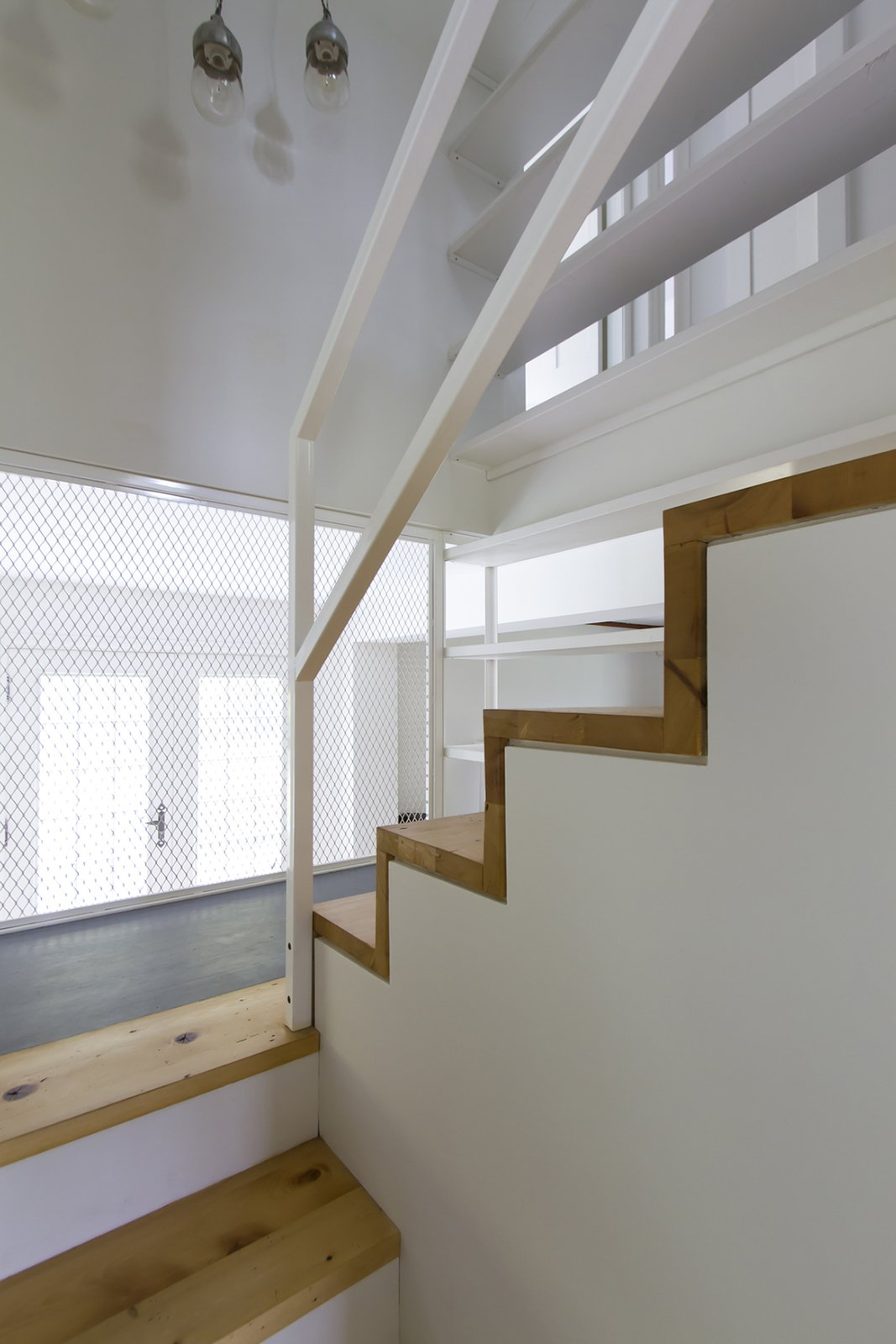 The staircase was built from the wooden beams that belonged to the structure of the ancestral floor. The stairs also integrate a library that goes from the bottom of the steps to the ceiling. Tagged: Staircase, Metal Tread, Wood Tread, and Metal Railing.  L'Eau Vive by FÉLIX & Co.