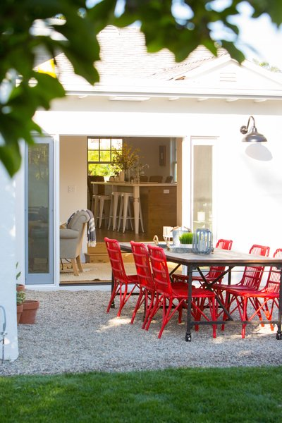 A set of bright red chairs with rustic barn table out back draw the eye through the house, while reinforcing the modern farmhouse story. Photo 4 of Modern Farmhouse modern home