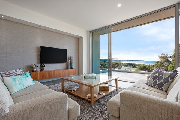 Living room with ocean views, blackwood veneer timber wall pod for storage with a soft ceramic tile textured wall below a bulkhead with lighting. Photo  of The Tathra Residence modern home