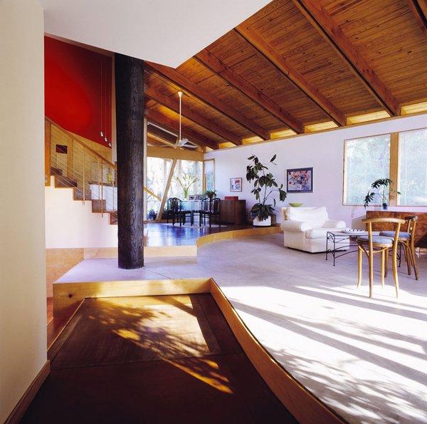 Modern home with living room, chair, recliner, pendant lighting, concrete floor, and medium hardwood floor. Photo  of Island Residence
