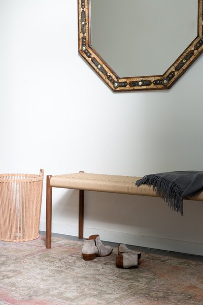 Entry featuring a DWR bench, vintage Turkish rug, and Moroccan mirror. Photo  of Laurel Heights Residence modern home