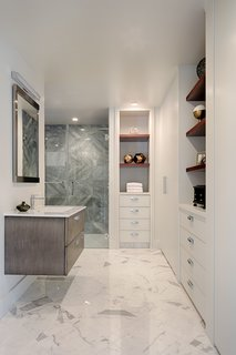 8 Spa-Like Bathrooms Designed to Instantly Soothe - Photo 3 of 8 - A functional and contemporary master bath becomes a spacious oasis with Afyon Grey marble in the shower, his-and-hers back-to-back vanities, and plenty of custom shelving and storage.