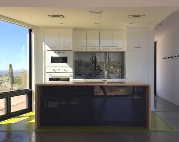 Modern home with back yard, garden, front yard, side yard, rooftop, slope, field, desert, woodland, trees, shrubs, chair, recliner, ceiling lighting, sun room, table, floor lighting, table lighting, wall lighting, and light hardwood floor. Photo 5 of Tucson Retirement Oasis