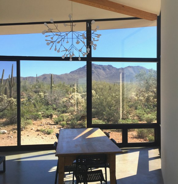 Modern home with front yard, rooftop, side yard, back yard, garden, field, slope, desert, trees, woodland, recliner, ceiling lighting, sun room, shrubs, chair, and dining room. Photo 4 of Tucson Retirement Oasis