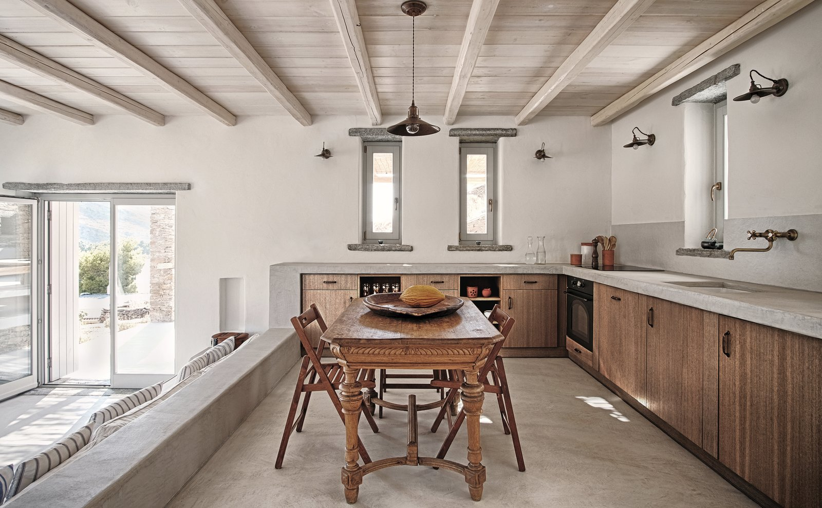 Kitchen area Tagged: Dining Room, Chair, Table, Pendant Lighting, and Concrete Floor.  ROCKSPLIT house by COMETA ARCHITECTS
