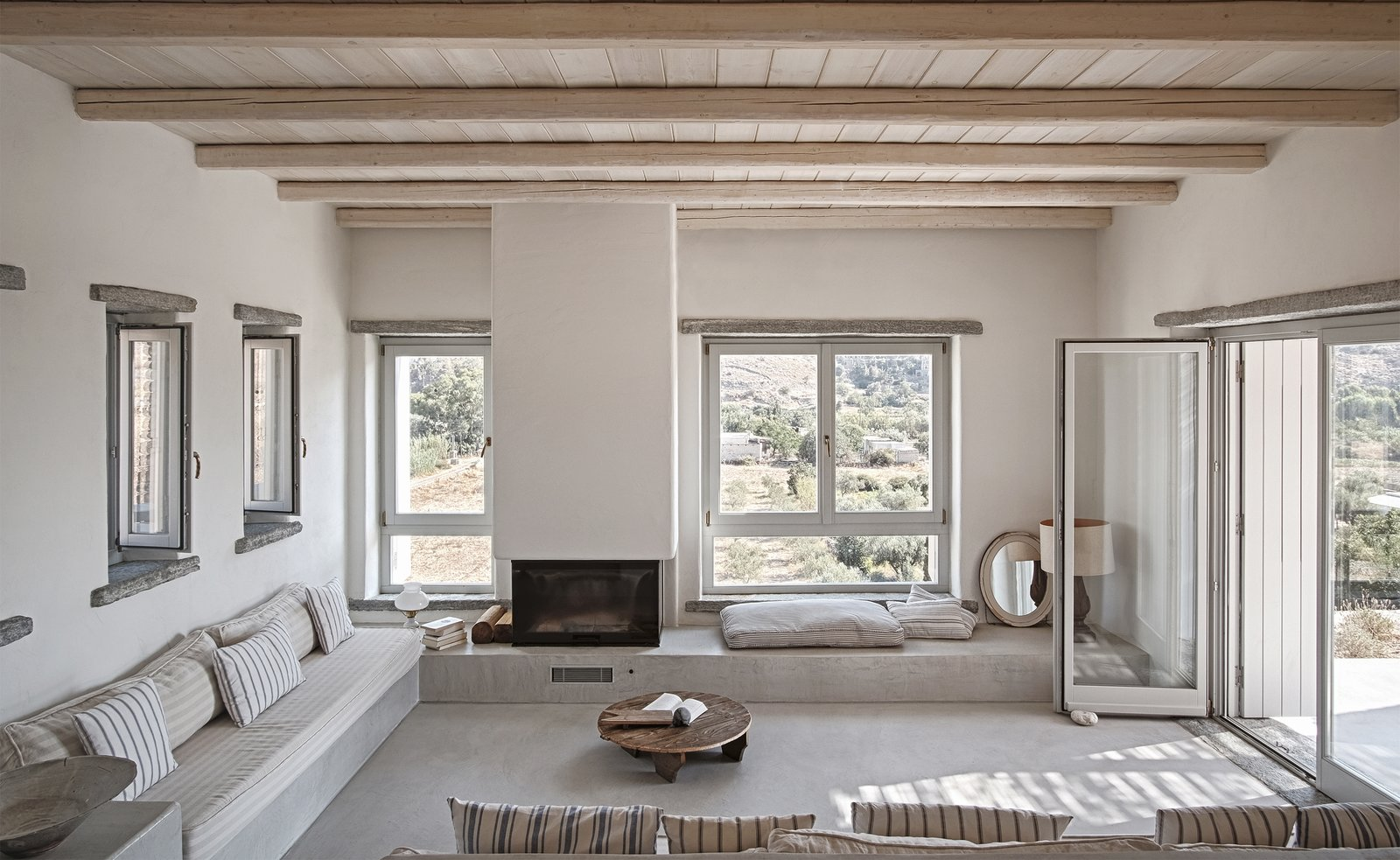 Living area Tagged: Living Room, Bench, Coffee Tables, Concrete Floor, Standard Layout Fireplace, and Wood Burning Fireplace.  ROCKSPLIT house by COMETA ARCHITECTS