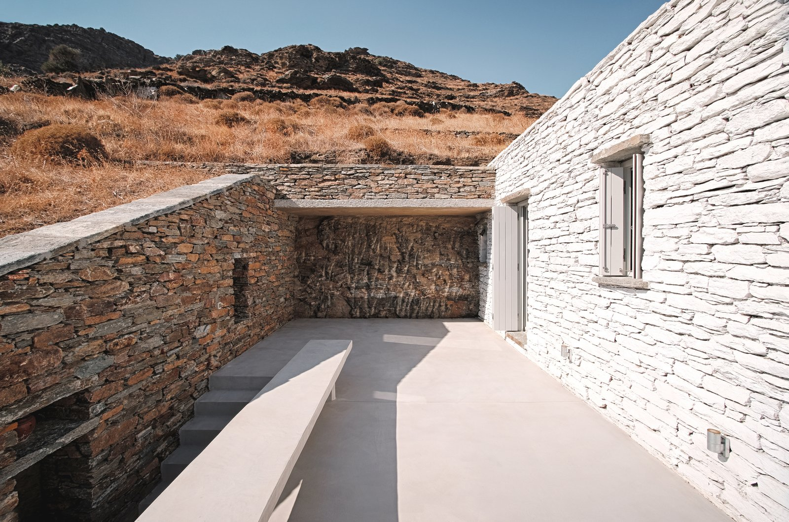 Cutting through the rock, upper bedroom terrace  ROCKSPLIT house by COMETA ARCHITECTS