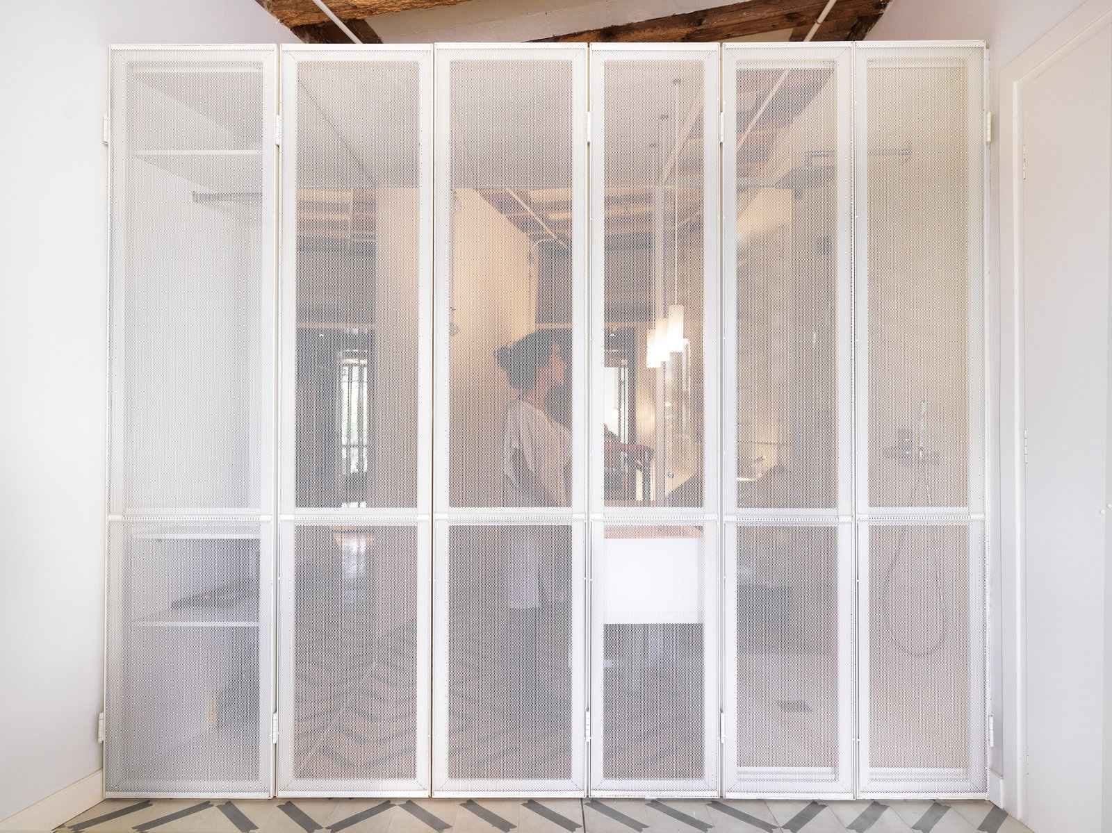 The Lightox, A perforated metal screen separates the living space from the private zone, allowing all natural ight to enter
