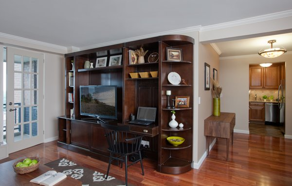 We added a new header over the space that connects the living room into the foyer in order to help define the space. We also added some crown and base moldings, and new wood floors throughout for a richer, more detailed look.  Photo 4 of Dog Lover's Apartment modern home